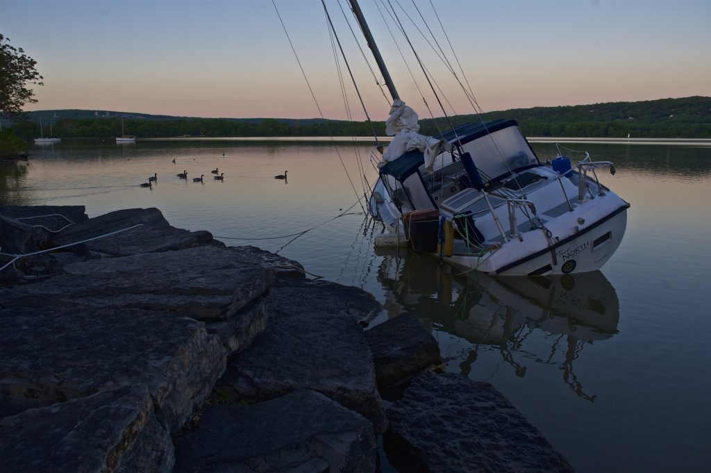 A sailboat needing attention lists to the port, moored on the rocks at East Shore Park in Ithaca, perhaps having run aground.